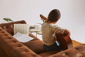 girl taking guitar lessons for beginners on sofa and music sheet